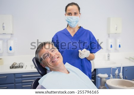 Dentist wearing surgical mask with a smiling patient in dental clinic - stock photo