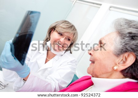 Dentist with an elder female patient looking at an x-ray - stock photo