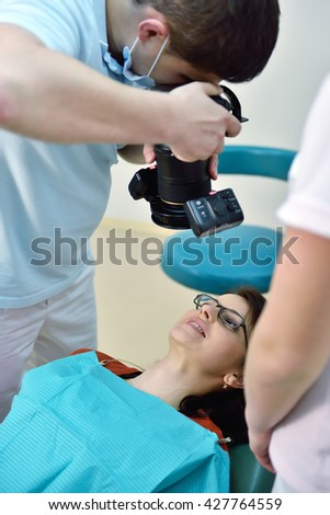 Dentist with camera shooting of patients smile after treatment. - stock photo
