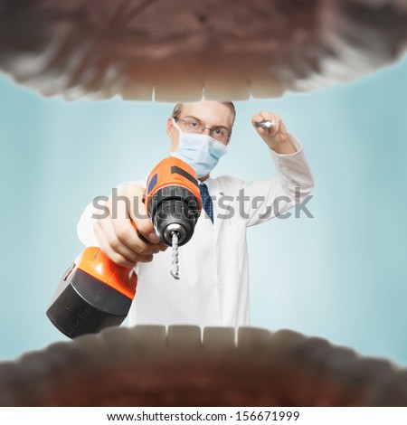Dentist with electric drill symbolizing fear of pain. - stock photo
