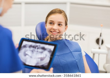 dentist with x-ray on tablet pc and girl patient