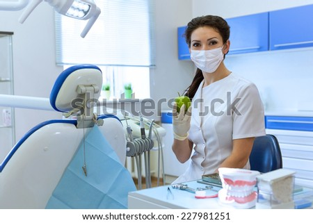 Dentist woman in mask at stomatology office holding green apple. Health care concept - stock photo
