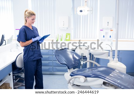 Dentist working on tablet pc at the dental clinic - stock photo