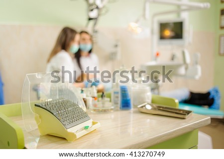 Dentistry drills, polishers and polishing brushes eraser on foreground and female dentist with assistant doing first check-up on the background. Stomatology equipment at the dental clinic. Dentistry - stock photo