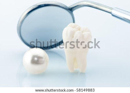 Dentistry. Wisdom tooth, natural pearl and dental mirror - stock photo