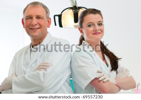 Dentists in their surgery looking at the viewer standing side by side - stock photo