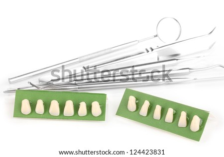 denture with dental tools isolated on white