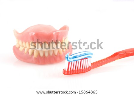 Dentures and toothbrush with toothpaste isolated on white. - stock photo