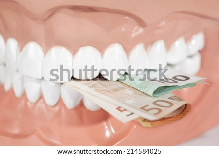 Dentures biting euro banknotes close up - stock photo