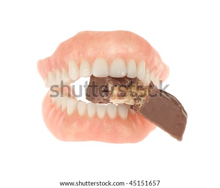 Dentures chewing on a chocolate candy bar isolated on white - stock photo