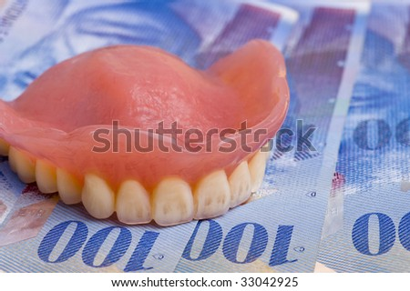 dentures on swiss franc bills with focus on the front teeth - stock photo