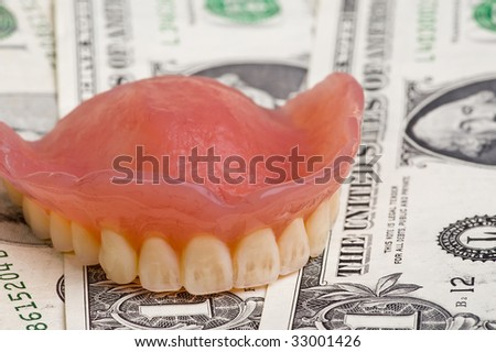 dentures on us dollar bills with focus on the front teeth - stock photo