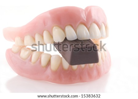 Dentures with piece of chocolate isolated on a white background.