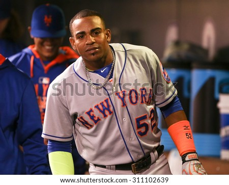 DENVER-AUG 21: New York Mets outfielder Yoenis Cespedes celebrates in the dugout after hitting a homerun against the Colorado Rockies at Coors Field on August 21, 2015 in Denver, Colorado. - stock photo