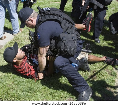 DENVER - AUGUST 26: A police officer tackles and arrests a protester during the Democratic National Convention August 26, 2008 in Denver. - stock photo