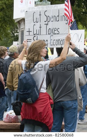 DENVER, COLORADO – APRIL 15: A woman holds up her anti-tax sign at a Tea Party Patriots Rally in Downtown Denver, April 15, 2011