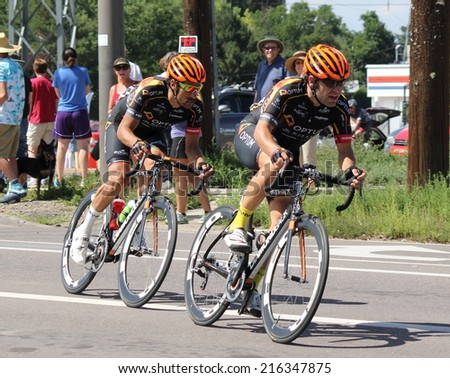 Denver, Colorado- August 24, 2014:  Team Optum riders Jesse Anthony (left) Tom Zirbel race in the USA pro cycling challenge on Stage 7 from Boulder to Denver. - stock photo