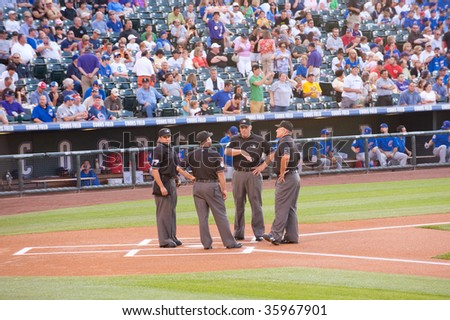 DENVER, COLORADO - AUGUST 11: Umpires gather at home plate prior to the start of the Colorado Rockies baseball game on August 11, 2009 in Denver Colorado.