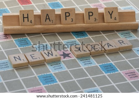 "Denver, Colorado - December 31, 2014:  ""Happy New Year"" concept spelled out in wooden Scrabble letters on wooden rack and Scrabble game  board  - stock photo"
