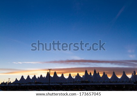 Denver, Colorado-January 19, 2013:Tents of DIA at sunrise. Denver International Airport well known for peaked roof. Design of roof is reflecting snow-capped mountains. - stock photo