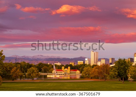 Denver Colorado skyline from City Park with City Park Boathouse and Rocky Mountains in background on autumn morning - stock photo