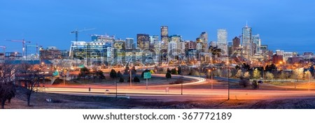 Denver, Colorado, USA - December 09, 2015: After sunset, colorful lights of skyscrapers bright up the skyline of Downtown Denver; its streets and highways are filled with heavy rush-hour traffic.  - stock photo