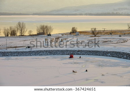 Denver, Colorado, USA - December 31, 2015: It is a very cold December evening; a few people are enjoying ice fishing on the frozen lake at Chatfield State Park. - stock photo