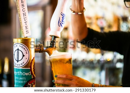 Denver, Colorado, USA-June 3, 2015. Bartender pouring draft beer in the bar. - stock photo