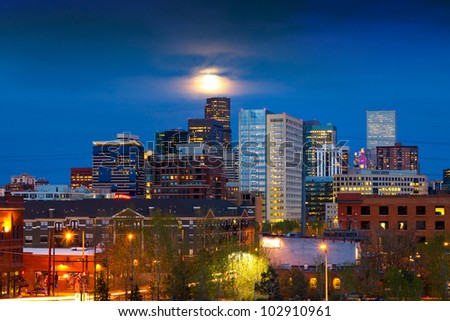 Denver skyline at dusk with the full moon rising above - stock photo