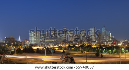 Denver skyline at night. Summer 2010. Focus on skyscrapers. Automobile traffic lights in foreground - stock photo