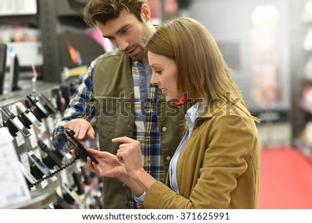 Department store seller assisting customer with buying new phone - stock photo