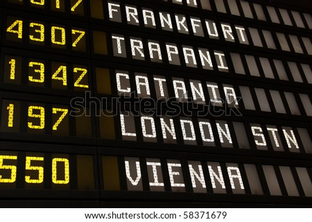 Departure board at an airport in Italy. Flights to Frankfurt, Trapani, Catania, London and Vienna - stock photo