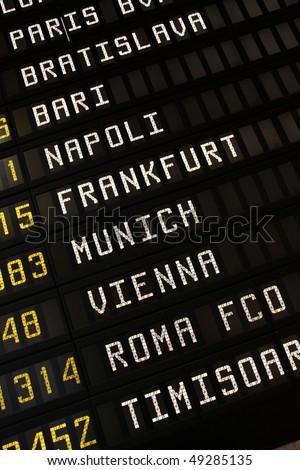 Departure board at an airport in Italy. Flights to Paris, Bratislava, Bari, Napoli (Naples), Frankfurt, Munich, Vienna and Rome. - stock photo