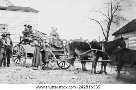 DEPARTURE FROM THE OLD HOMESTEAD, 1862 photograph by George Barnard shows a American family on the move during the Civil War. The pipe smoking woman may be a descendant of early Scotch-Irish settlers. - stock photo