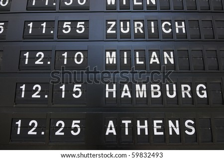 Departure times on an analog sign. - stock photo