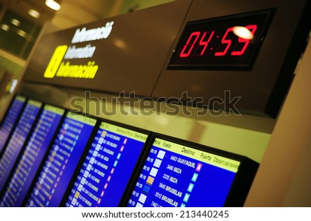 Departures display board at airport terminal showing international destinations flights to some of the world's most popular cities - stock photo