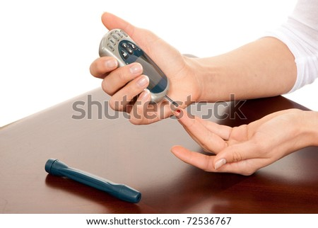 Dependent first type Diabetic patient measuring glucose level blood test using smart mini glucometer and small drop of blood from finger and test strips isolated on a white background - stock photo