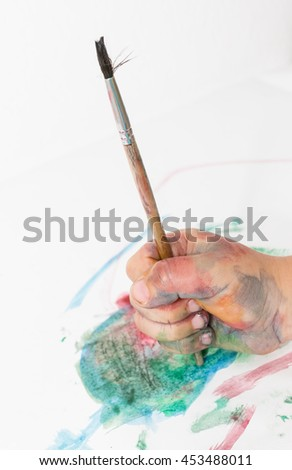 depicting children's hands in the paint with a brush