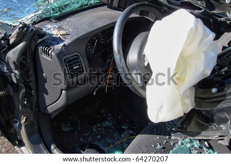 Deployed crash safety air bag in a heavily damaged wrecked car after a violent traffic accident