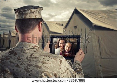 Deployed Military Man Chats With Family on Computer - stock photo