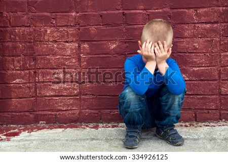 Depressed abused poor crying little child (boy, kid) sitting near big red brick wall - stock photo