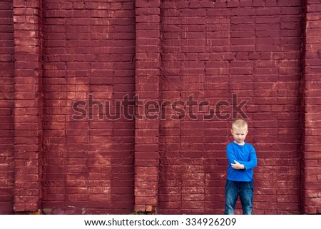 Depressed abused poor little child (boy, kid) sitting near big red brick wall - stock photo