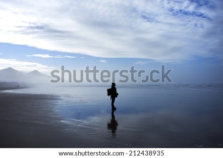 Depressed and lonely man looking out into the sea - stock photo
