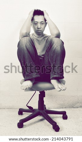 Depressed asian man sitting in the chair on dark color - stock photo