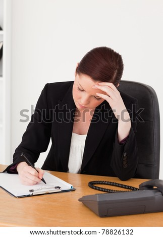 Depressed beautiful red-haired woman in suit writing on a notepad while sitting in an office