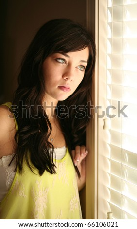 depressed beautiful young female model looking out window - stock photo