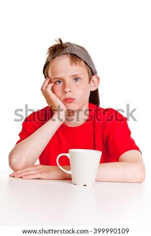 Depressed boy in red shirt, gray hat and hand on cheek with bored expression sitting in front of large ceramic mug over white background