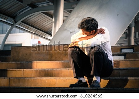 Depressed business man sitting at the stairs