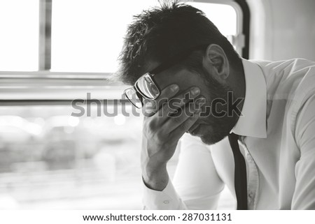 Depressed business man traveling home by train  - stock photo