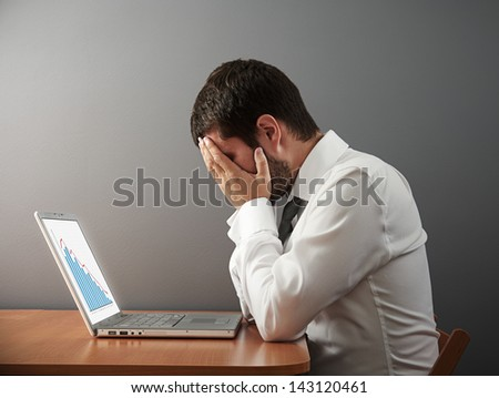depressed businessman covering his face by the hands over dark wall - stock photo